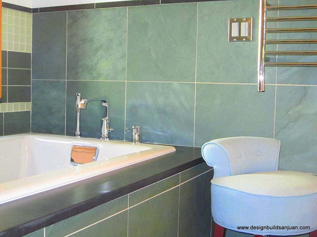 Large tiles were installed on the walls and surrounding the bathtub of this custom bathroom.