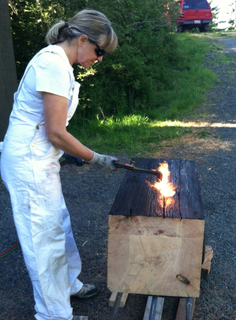 Woman wearing safety goggles applies fire to a cut slab of of wood outdoors.