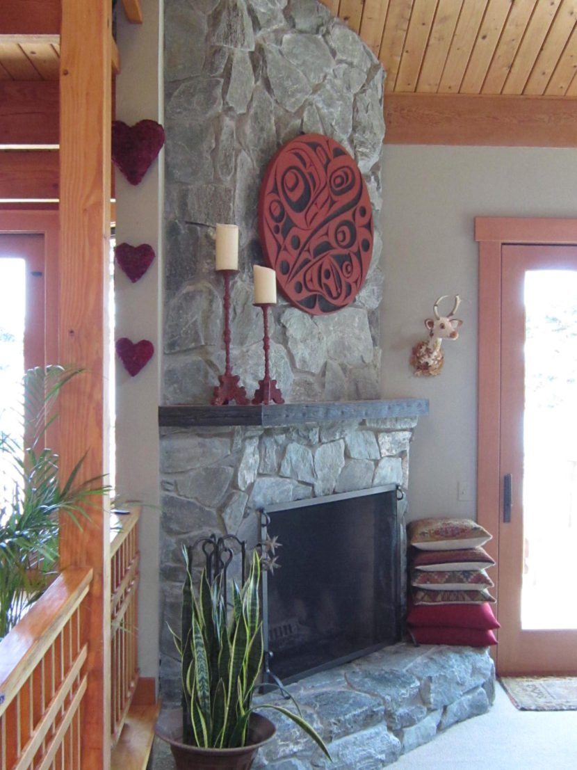 A custom wood mantle made of douglas fir sitting atop a stone fireplace.