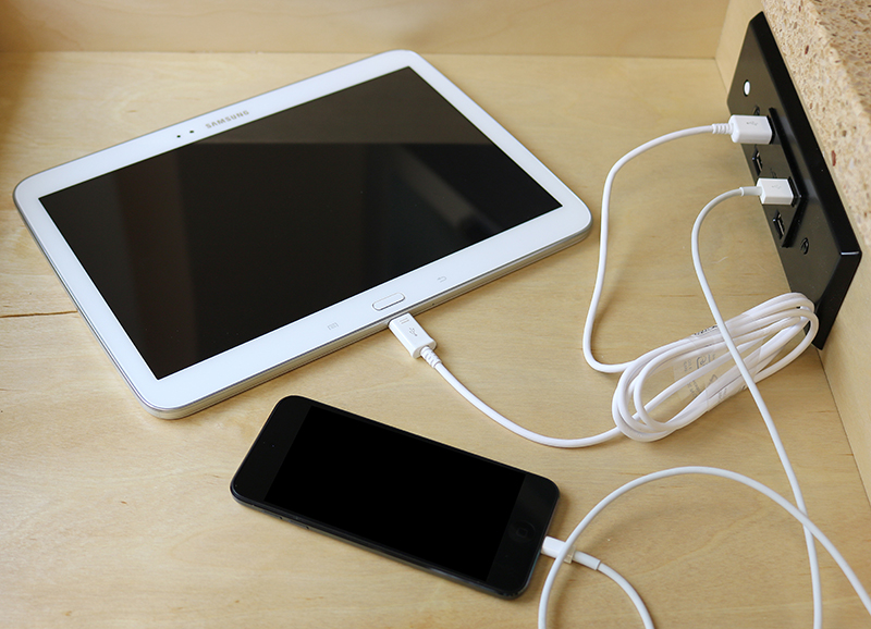 A tablet and phone are plugged into an outlet that is built into a countertop.